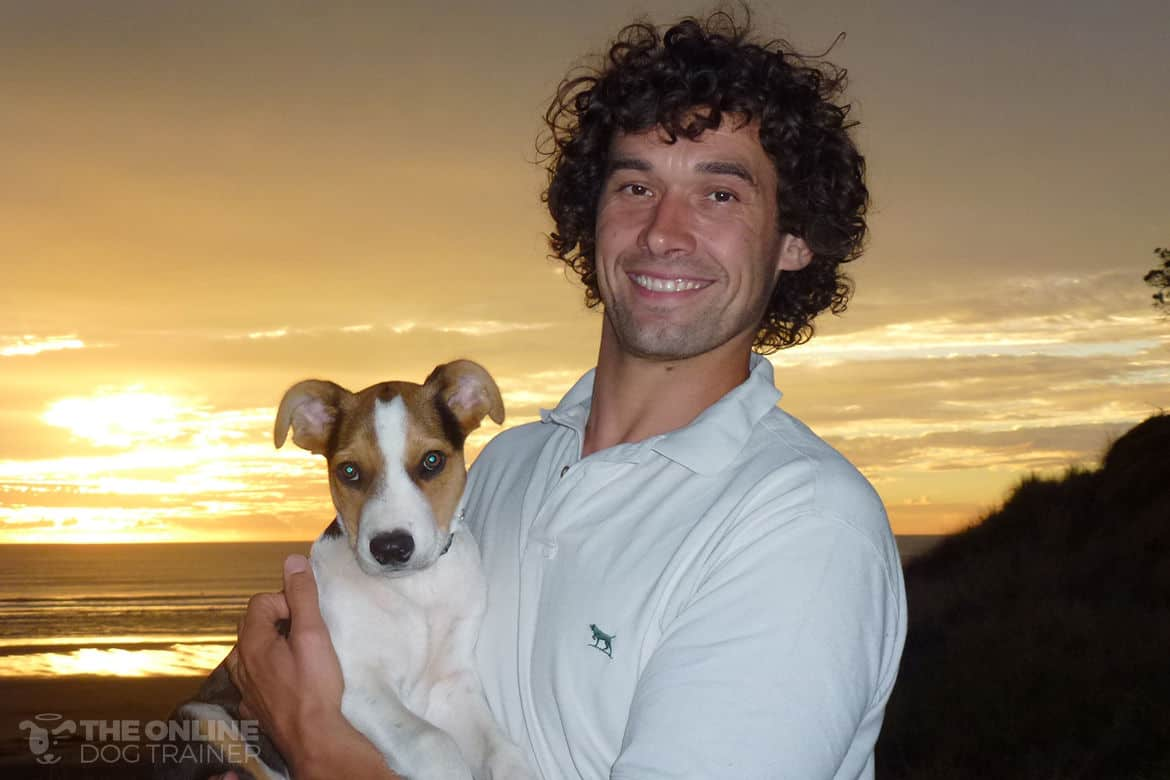 Doggy dan holding puppy Moses against a sunset background